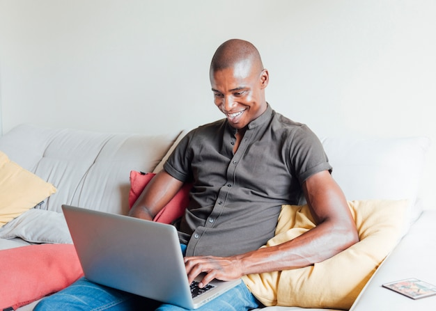 Lächelnder hübscher rasierter junger mann, der auf sofa unter verwendung des laptops sitzt Kostenlose Fotos