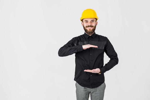 Lächelnder ingenieur, der das gelbe hardhatgestikulieren trägt Kostenlose Fotos
