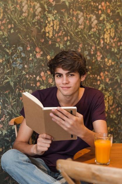 Lächelnder jugendlicher, der im café liest Kostenlose Fotos