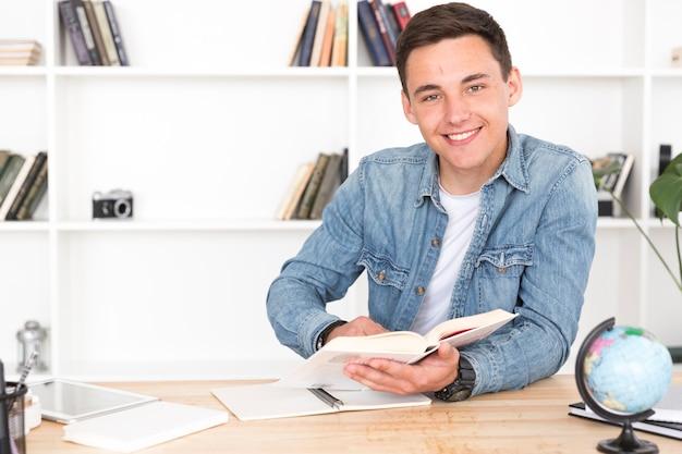 Lächelnder jugendlicher, der im klassenzimmer studiert Kostenlose Fotos