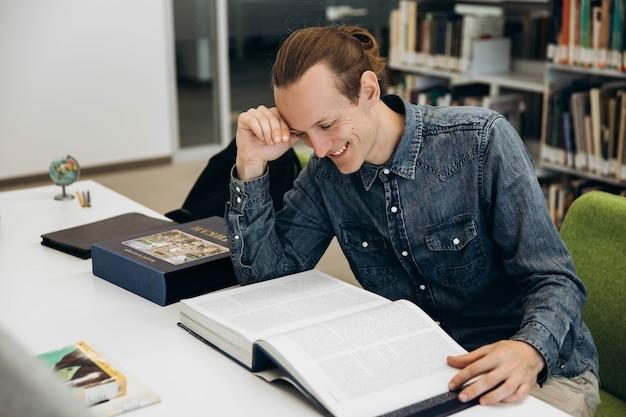 Lächelnder junge arbeitet mit buch am tisch in der bibliothek Premium Fotos