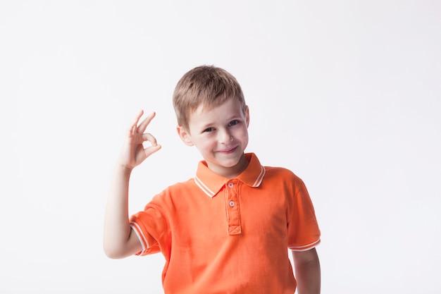 Lächelnder junge, der das orange t-shirt gestikuliert okayzeichen auf weißem hintergrund trägt Kostenlose Fotos