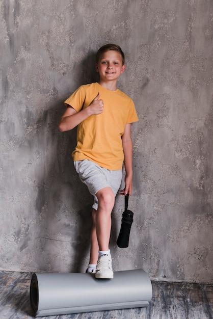 Lächelnder junge, der vor der betonmauer sich zeigt daumen steht Kostenlose Fotos