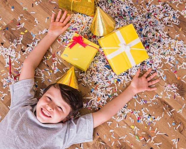 Lächelnder junge im geburtstagshut, der mit geschenken und konfettis auf boden liegt Kostenlose Fotos