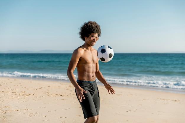 Lächelnder junger afroamerikanermann, der fußball auf seeküste spielt Kostenlose Fotos