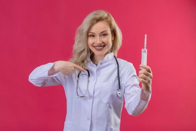 Lächelnder junger arzt, der stethoskop im medizinischen kleid trägt spritze hält und sich auf roten hintergrund zeigt Kostenlose Fotos