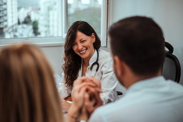 Lächelnder junger doktor, der mit jungen paaren sich berät. Premium Fotos
