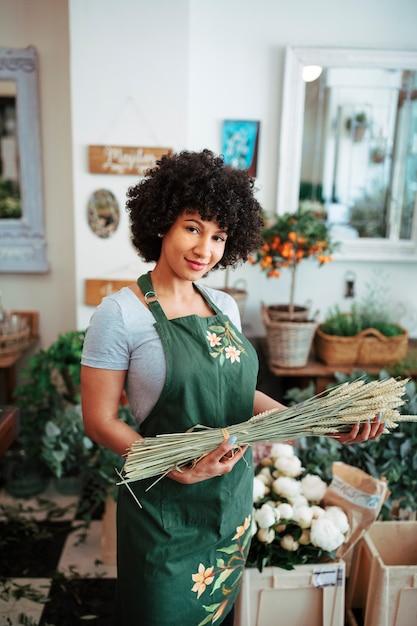 Lächelnder junger florist, der ährchen im shop hält Kostenlose Fotos