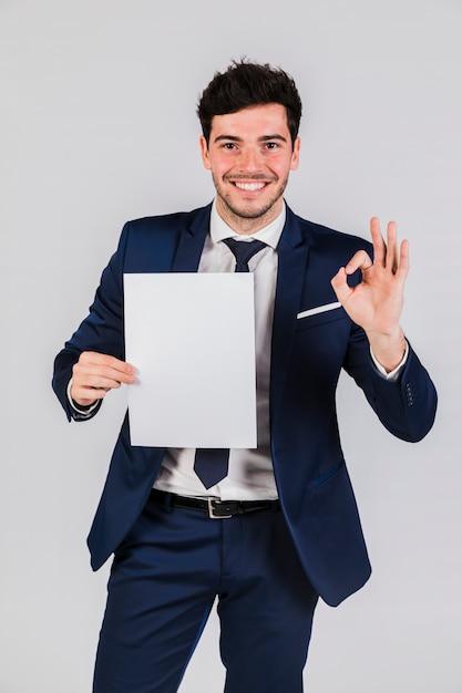 Lächelnder junger geschäftsmann, der das weißbuch in der hand zeigt okayzeichen hält Kostenlose Fotos