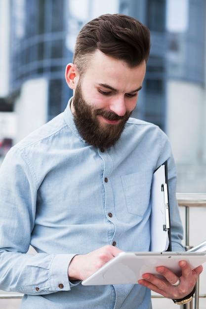 Lächelnder junger geschäftsmann, der klemmbrett unter verwendung der digitalen tablette hält Kostenlose Fotos