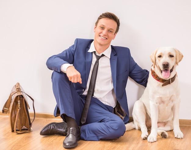 Lächelnder junger geschäftsmann mit seinem hund, der auf boden sitzt. Premium Fotos