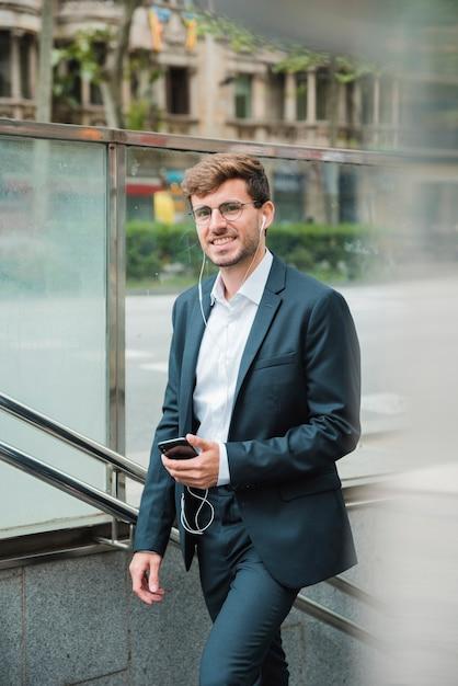 Lächelnder junger geschäftsmann mit seinem kopfhörer im ohr, das in der hand handy hält Kostenlose Fotos