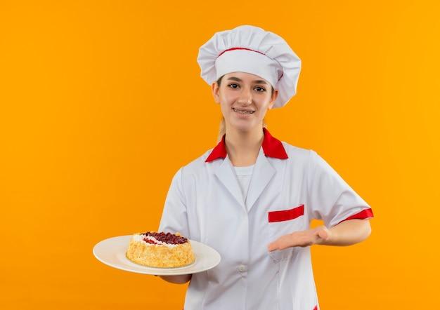 Lächelnder junger hübscher koch in der kochuniform mit zahnspangen, die mit hand auf teller des kuchens halten und auf orange raum lokalisiert halten Kostenlose Fotos