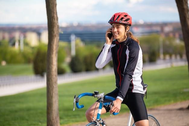 Lächelnder junger hübscher männlicher radfahrer in der sportkleidung und schutzhelm auf dem fahrrad, das am telefon im stadtpark spricht Premium Fotos