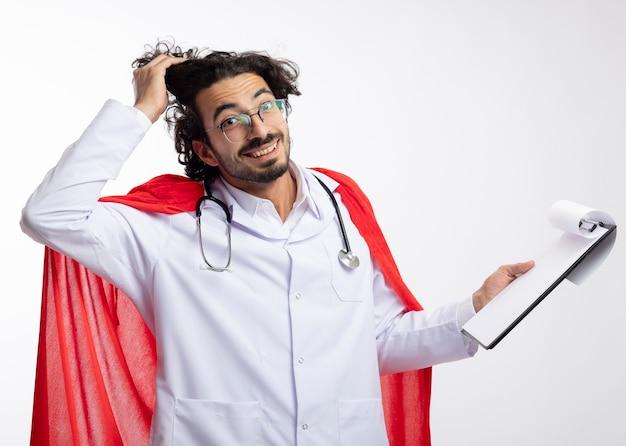 Lächelnder junger kaukasischer mann in der optischen brille, die arztuniform mit rotem umhang und mit stethoskop um hals trägt, hebt haar mit hand und hält klemmbrett an weißer wand Kostenlose Fotos