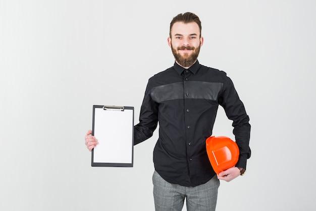 Lächelnder junger männlicher architekt, der hardhat und klemmbrett hält Kostenlose Fotos