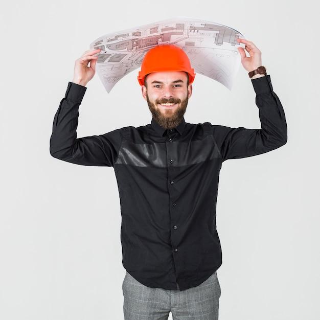 Lächelnder junger männlicher architekt, der plan über seinem kopf hält Kostenlose Fotos
