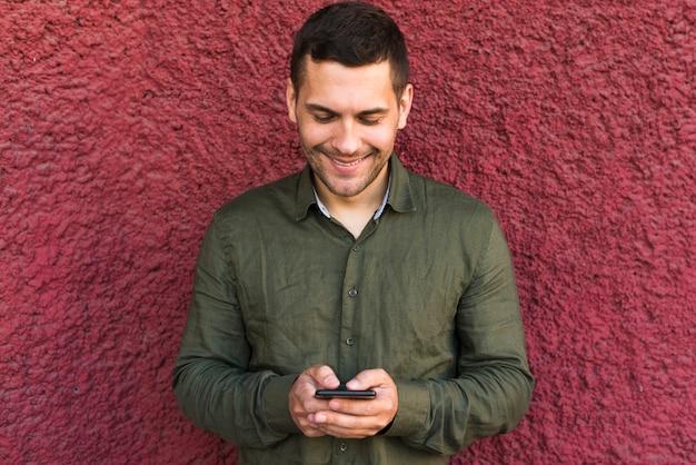 Lächelnder junger mann beschäftigt, wenn mitteilung zu jemand simst Kostenlose Fotos