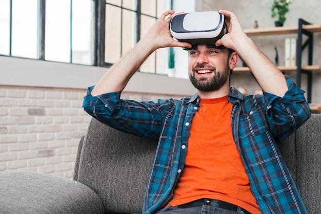 Lächelnder junger mann, der auf tragender kamera der virtuellen realität des sofas sitzt Kostenlose Fotos