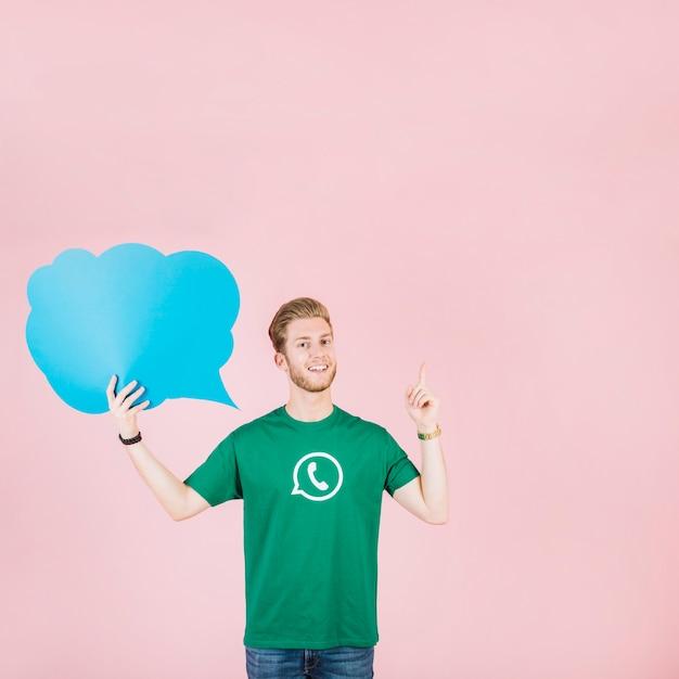 Lächelnder junger mann, der aufwärts zeigt, leere blaue spracheblase halten Kostenlose Fotos