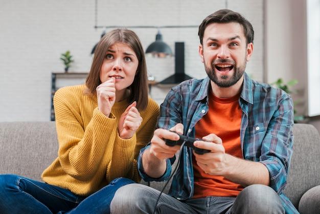 Lächelnder junger mann, der das videospiel mit ihrer frau spielt Kostenlose Fotos