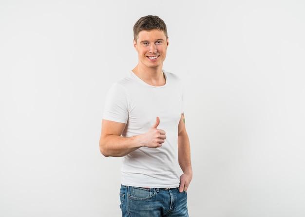 Lächelnder junger mann, der daumen herauf zeichen gegen weißen hintergrund zeigt Kostenlose Fotos