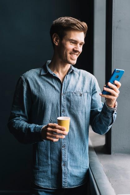 Lächelnder junger mann, der die mitnehmerkaffeetasse betrachtet mobiltelefon betrachtet Kostenlose Fotos