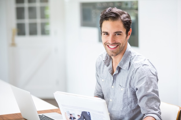 Lächelnder junger mann, der dokumente beim sitzen am schreibtisch mit laptop verwahrt Premium Fotos