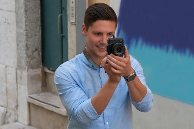 Lächelnder junger mann, der foto auf kamera in der straße macht Kostenlose Fotos