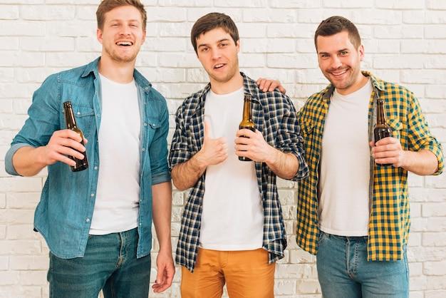 Lächelnder junger mann, der in der hand die bierflasche steht mit seinem freund zeigt daumen herauf zeichen hält Kostenlose Fotos