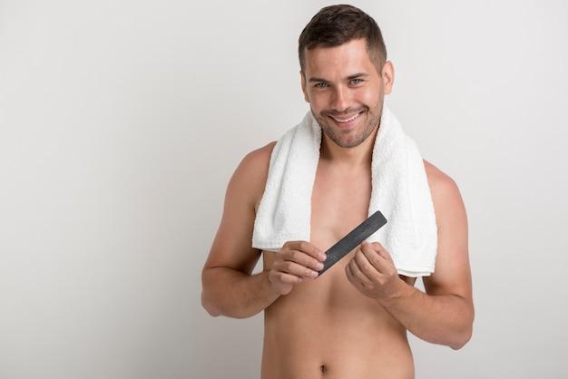 Lächelnder junger mann, der kamera beim polieren seiner nägel mit geldstrafe betrachtet Kostenlose Fotos