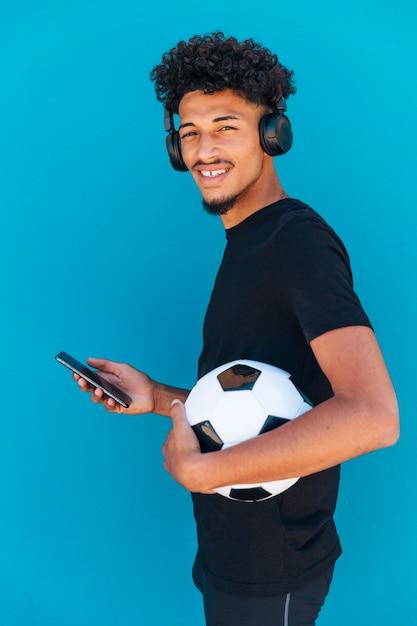 Lächelnder junger mann, der mit fußball und telefon steht Kostenlose Fotos