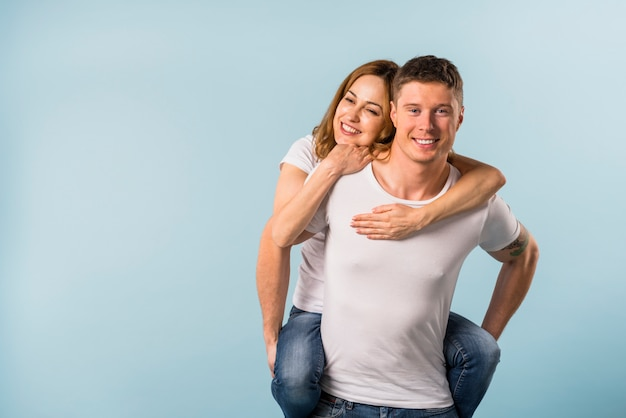 Lächelnder junger mann, der piggyback ihrer freundin gegen blauen hintergrund fahrt gibt Kostenlose Fotos