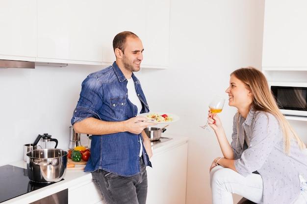Lächelnder junger mann, der salat und seinen trinkenden alkohol der frau isst Kostenlose Fotos