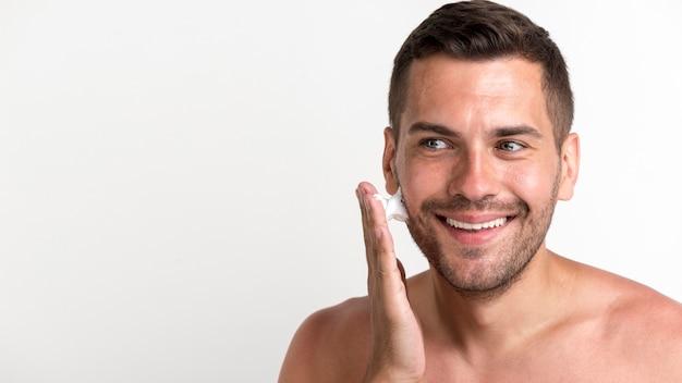 Lächelnder junger mann, der schaum gegen weißen hintergrund rasierend aufträgt Kostenlose Fotos