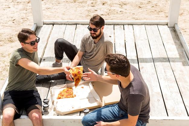 Lächelnder junger mann, der scheibe des pizzafreundes auf strand gibt Kostenlose Fotos