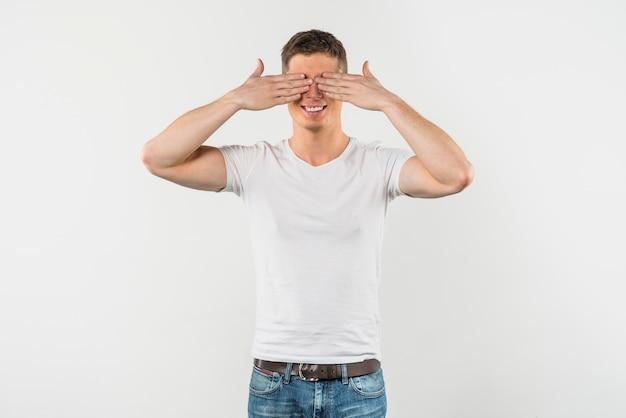 Lächelnder junger mann, der seine augen lokalisiert auf weißem hintergrund bedeckt Kostenlose Fotos