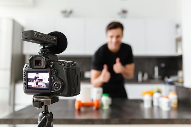 Lächelnder junger mann, der seine videoblogepisode filmt Kostenlose Fotos