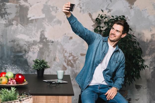 Lächelnder junger mann, der selfie vom mobiltelefon nimmt Kostenlose Fotos