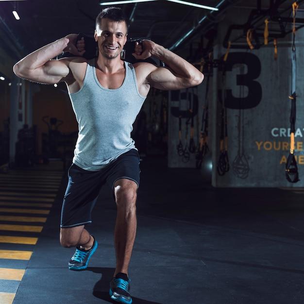 Lächelnder junger mann, der training in der turnhalle tut Kostenlose Fotos