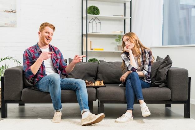 Lächelnder junger mann, der über ihrer freundin sich lustig macht, nachdem er das schachspiel im wohnzimmer gewonnen hat Kostenlose Fotos