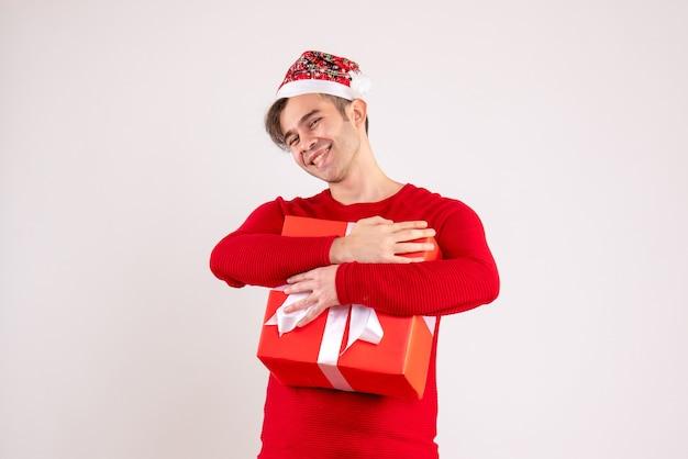 Lächelnder junger mann der vorderansicht mit der weihnachtsmütze, die sein geschenk auf weiß festhält Kostenlose Fotos