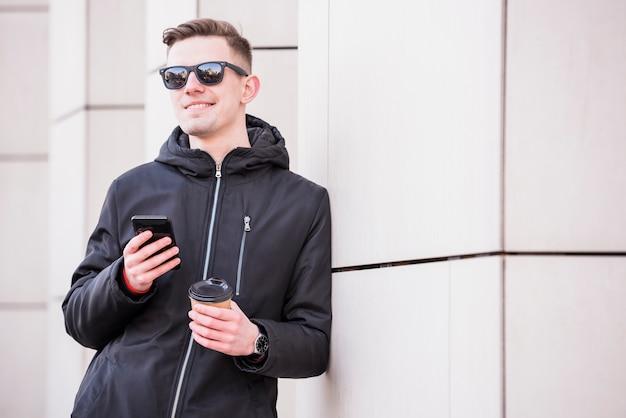 Lächelnder junger mann mit mobile in der hand halten mitnehmerkaffeetasse Kostenlose Fotos
