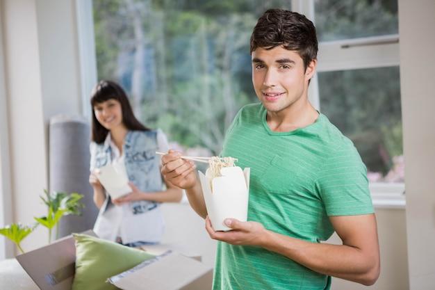 Lächelnder junger mann und frau, die zu hause nudeln essen Premium Fotos