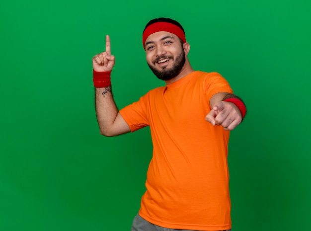 Lächelnder junger sportlicher mann, der stirnband und armband trägt, zeigt oben und an der kamera lokalisiert auf grün Kostenlose Fotos