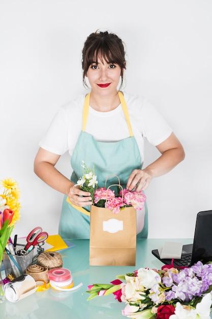 Lächelnder junger weiblicher florist mit blumenpapiertüte auf schreibtisch Kostenlose Fotos