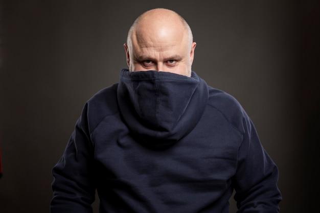 Lächelnder kahler mann in einem hoodie. humor. schwarz Premium Fotos