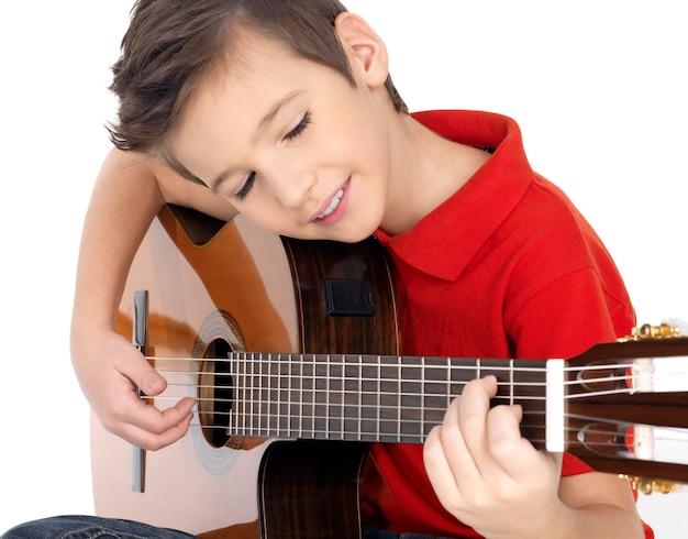 Lächelnder kaukasischer junge spielt die akustische gitarre - lokalisiert auf weißem hintergrund Kostenlose Fotos