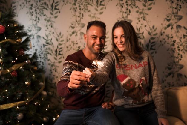 Lächelnder kerl nahe netter dame mit bengal beleuchtet nahe weihnachtsbaum Kostenlose Fotos