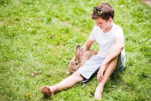 Lächelnder kleiner junge, der mit kaninchen auf grünem gras sitzt Kostenlose Fotos